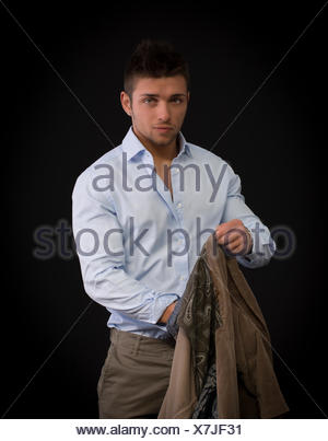 Handsome young man portrait, standing on dark background, with jacket in one hand - Stock Photo