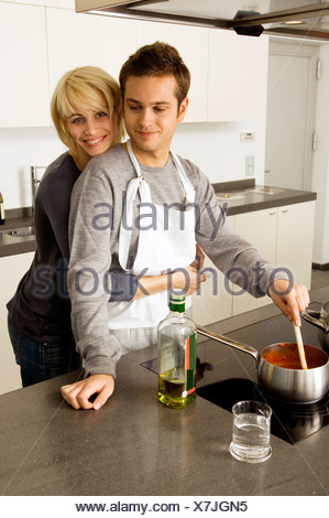 Young man cooking food and a young woman embracing him from behind in the kitchen - Stock Photo