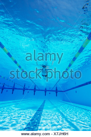 Underwater shot of male thlete swimming in pool - Stock Photo