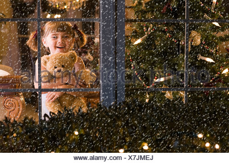 Little girl looking at snow - Stock Photo