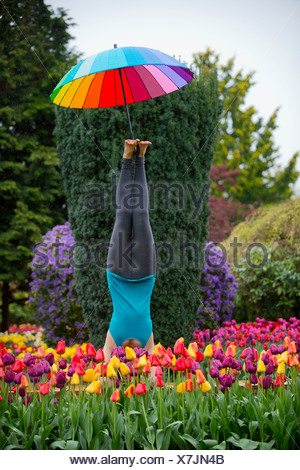 Woman with umbrella doing headstand - Stock Photo