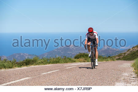 Man cycling on road, Corsica, France