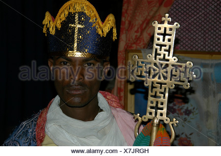Priest wearing a headdress and holding an artfully decorated cross, Rock Church in Lalibela, Ethiopia, Africa - Stock Photo