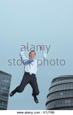 Businessman jumping for joy outdoors - Stock Photo