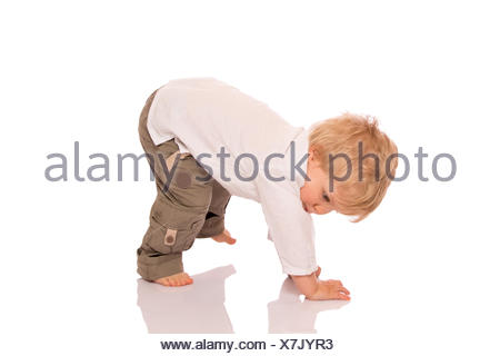 Young boy learning to walk - Stock Photo