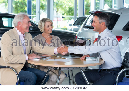 Smiling salesman and couple shaking hands at table in car dealership showroom - Stock Photo