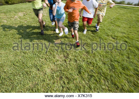 View of children's feet running towards the viewer - Stock Photo