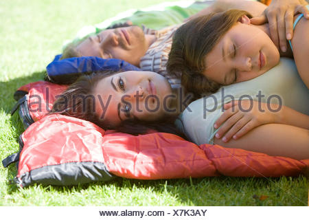 Family lying on sleeping bags in tent entrance on garden lawn, girl (7-9) sleeping on mother's chest, woman smiling, side view, portrait - Stock Photo