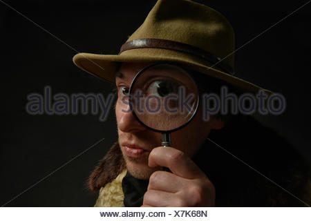 Man holding magnifying glass in front of his eye, Switzerland - Stock Photo