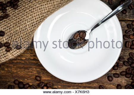 Coffee beans on spoon with white plate and surrounding coffeebeans - Stock Photo