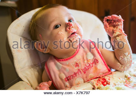 Close-Up Of Cute Baby Girl With Birthday Cake On Face At Home - Stock Photo