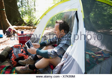 Man using digital tablet in camping tent - Stock Photo