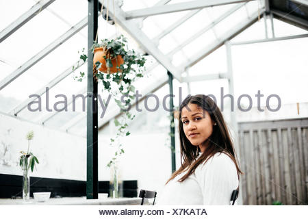 Portrait of young woman sitting in restaurant - Stock Photo