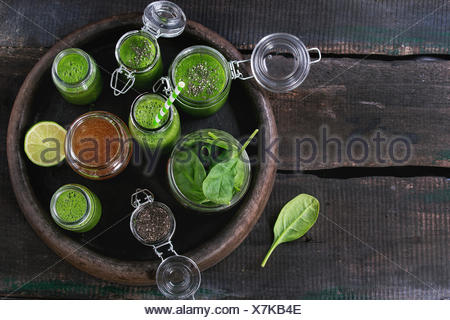 Opened glass jars and bottle of green spinach smoothie, served with baby spinach leaves, chia seeds, honey and lime in dark clay - Stock Photo