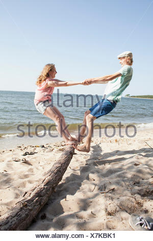 Friends enjoying while standing on driftwood at beach against clear sky - Stock Photo