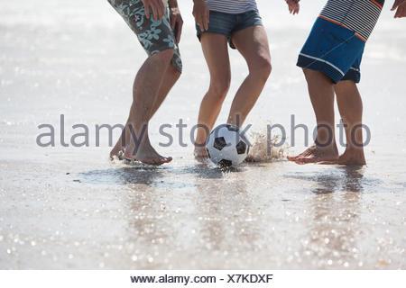 Friends playing football on beach - Stock Photo