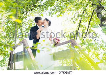Romantic newlywed mid adult couple kissing on footbridge in park - Stock Photo