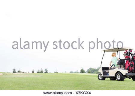 Couple sitting in golf cart against clear sky - Stock Photo