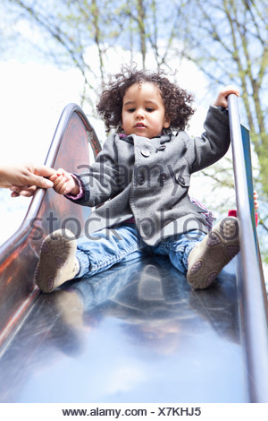 Girl playing on slide in playground - Stock Photo