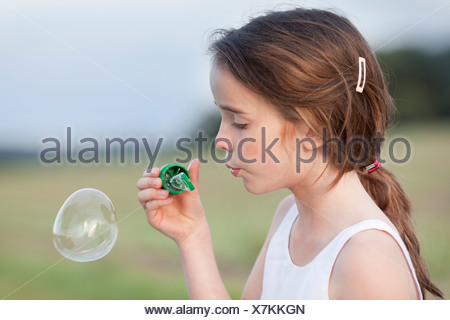 young girl playing with soap bubbles - Stock Photo