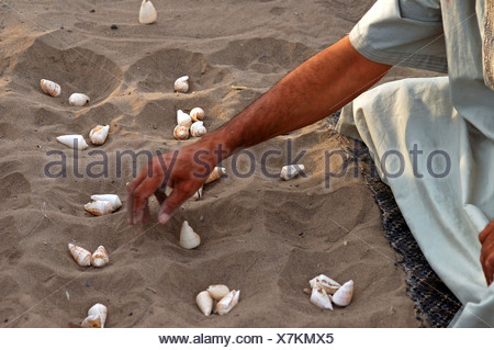Man playing Shell Hawalis, the Omanian version of Mancala, Sultanate of Oman, Middle East - Stock Photo