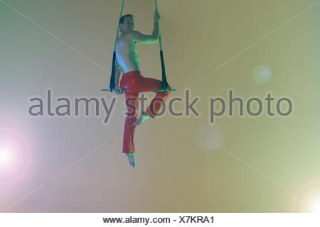 Trapeze artist sitting on trapeze - Stock Photo