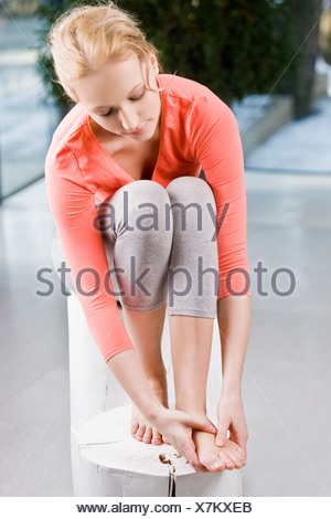 Young woman massaging feet - Stock Photo