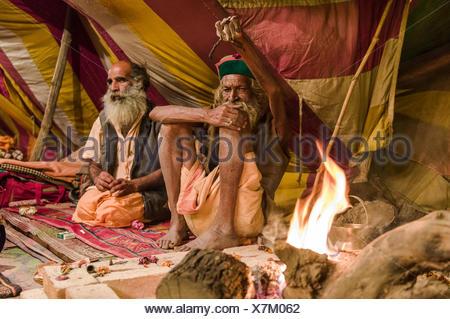Naga Sadhu sits by his sacred fire inside tent at Varanasi