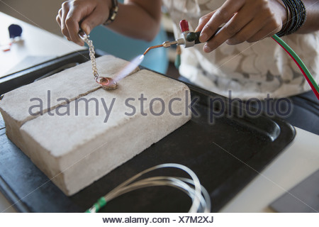 Close-up of woman's hands using hand torch to make jewelry - Stock Photo