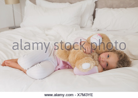 Young girl with stuffed toy resting in bed - Stock Photo