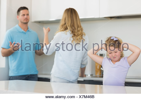 Girl covering ears while parents arguing - Stock Photo