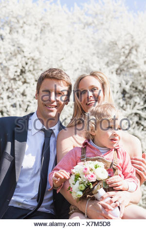 Newlywed couple with their son sitting in front of blossom tree, Munich, Bavaria, Germany - Stock Photo