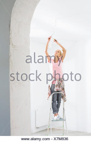 Woman on ladder fitting light bulb in new house - Stock Photo