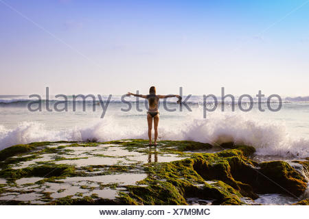 Indonesia, Bali, Woman standing in front of sea - Stock Photo