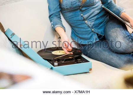 Cropped shot of young woman sitting on sofa listening to vintage record player - Stock Photo