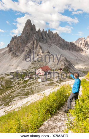 Hicker admire the Paterno Mount and Locatelli refuge. Sesto Dolomites, Trentino Alto Adige, Italy, Europe - Stock Photo