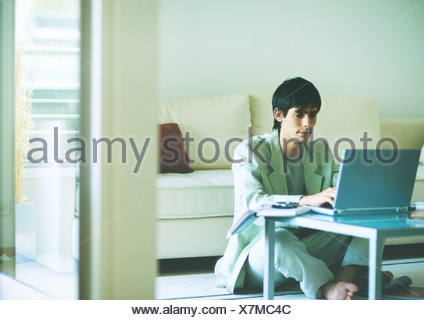 Young man sitting on floor, using laptop on coffee table - Stock Photo