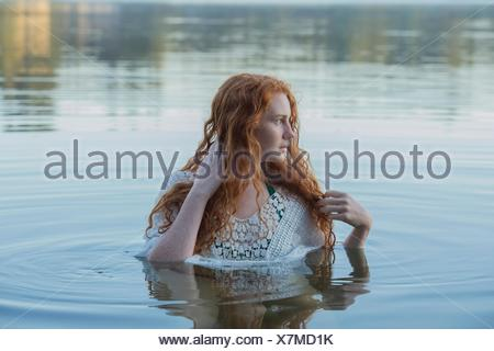 Head and shoulders of young woman with long red hair in lake looking sideways - Stock Photo