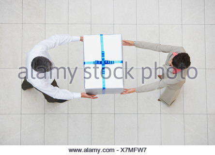 Overhead view of businessman and woman with gift box - Stock Photo