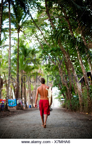 A man wearing red shorts walks down a dirt road carrying a surfboard. - Stock Photo