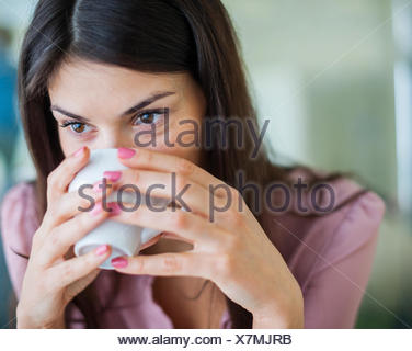 Young businesswoman having coffee in office - Stock Photo