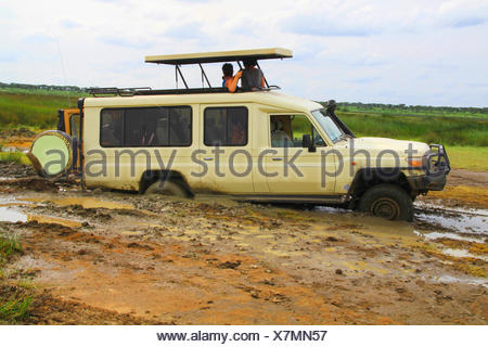 safari car sticking fast in the mud, tourists waiting for help, Tanzania, Serengeti National Park - Stock Photo