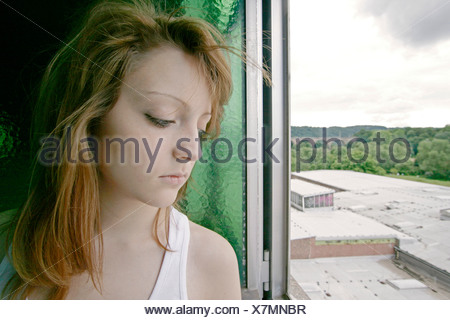 melancholy redheaded young woman looking out of opened window, Germany - Stock Photo