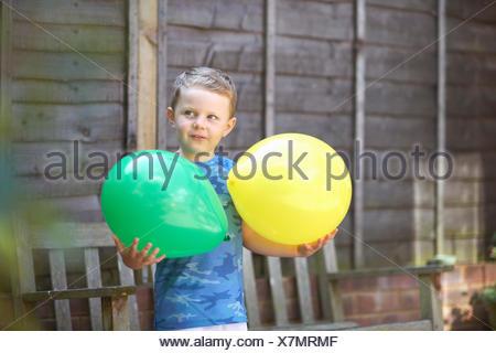 Young boy in garden, holding balloons - Stock Photo