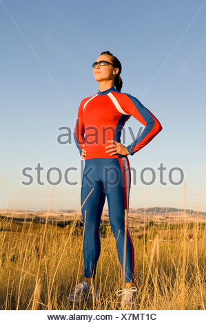 Woman wearing tracksuit standing in field - Stock Photo