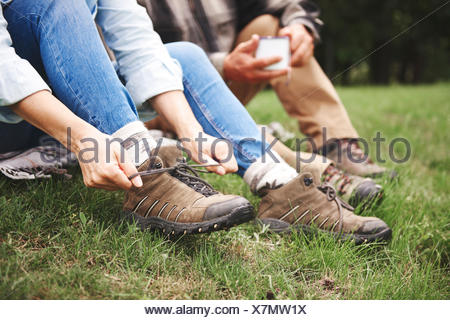 Mature couple sitting on grass, woman tying walking boots, low section - Stock Photo