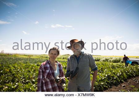 Portrait confident farmers harvesting zucchini in crop on sunny farm - Stock Photo
