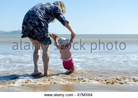Mother and baby daughter walking in surf at the beach, rear view