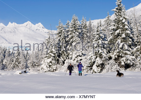 Women w/dog cross-country skiing along frozen Mendenhall River Tongass National Forest AK Winter - Stock Photo