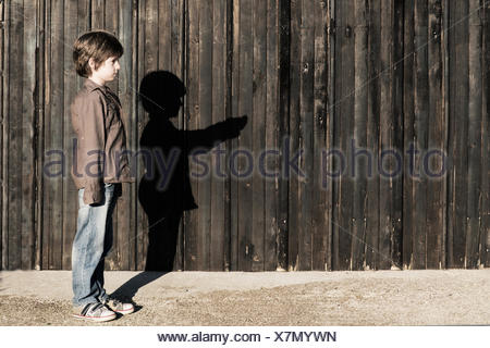 Boy standing next to a wooden fence with alter ego shadow - Stock Photo